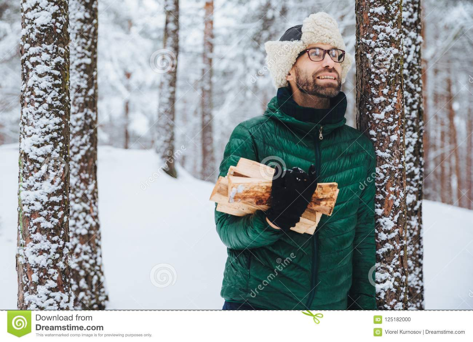 O retrato exterior de suportes masculinos de sorriso perto da árvore coberta com a neve, guarda a lenha, olha felizmente ascenden