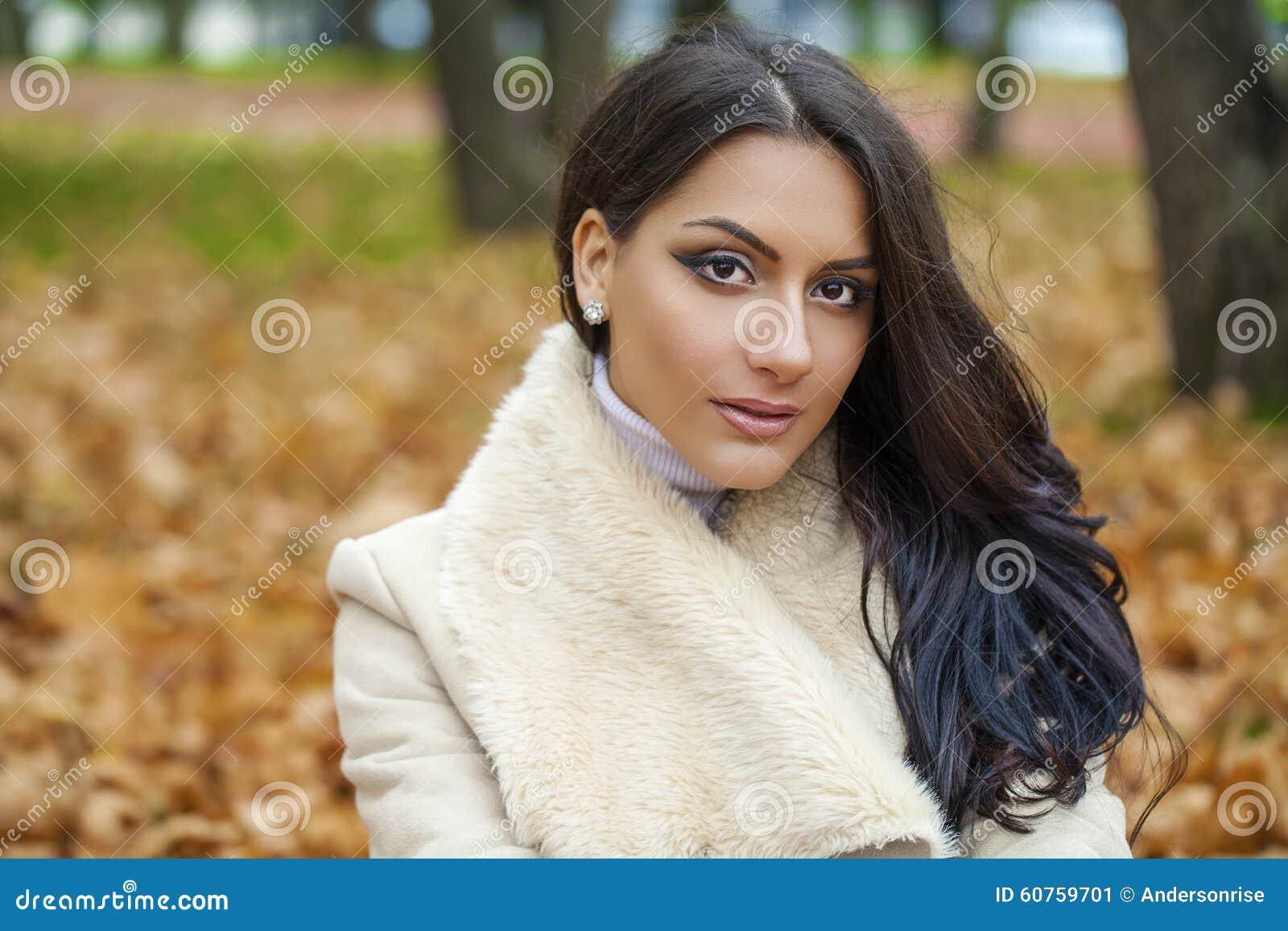 O retrato facial de uma mulher árabe bonita vestiu calorosamente exterior