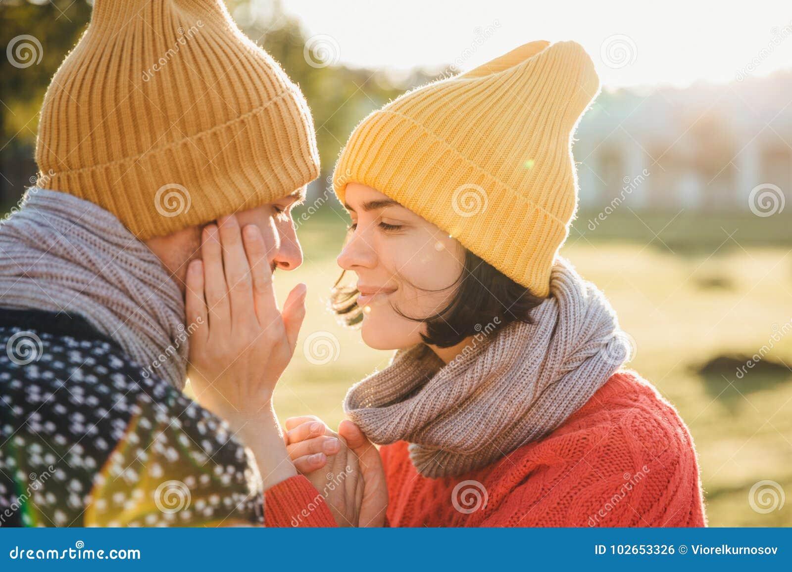 O retrato horizontal da fêmea moreno no chapéu morno, lenço e camiseta, mantém as mãos no mordente do ` s do noivo, tem o momento