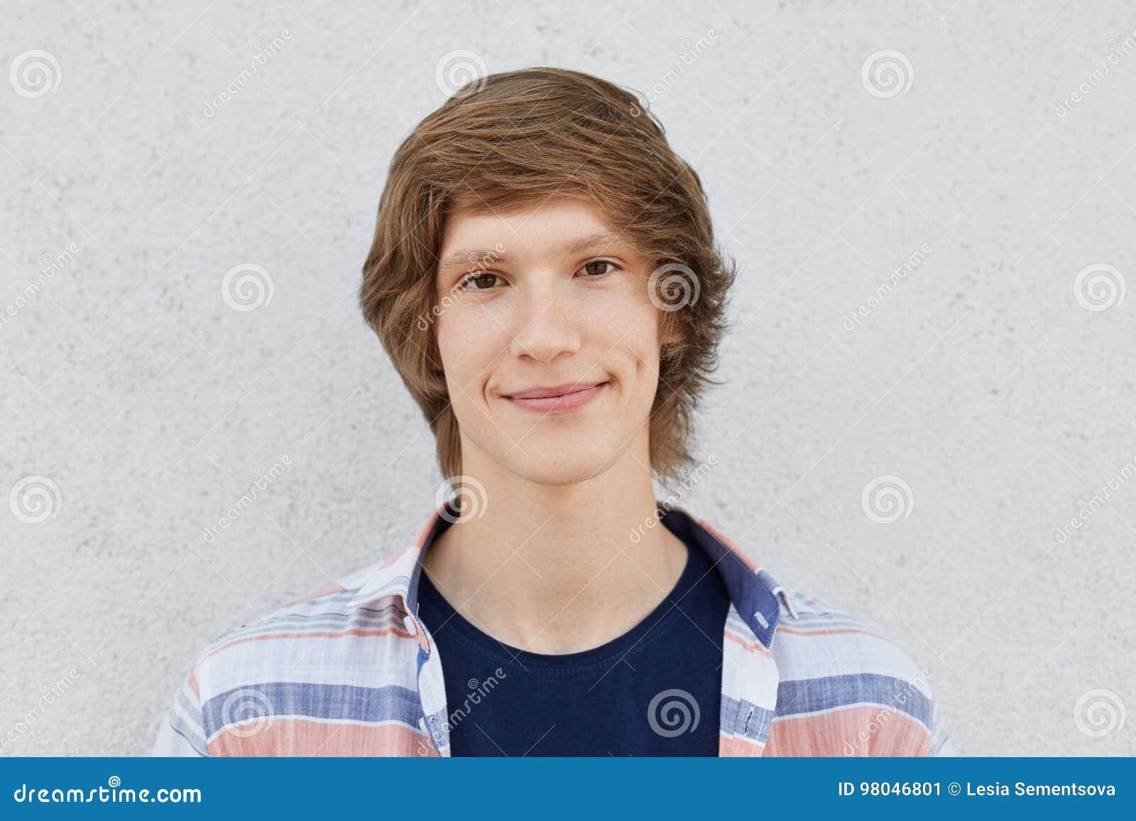 O retrato horizontal do adolescente masculino considerável com olhos escuros, ondulações em mordentes, tendo o penteado na moda,