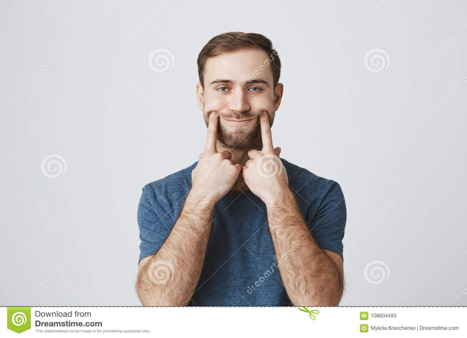 O retrato horizontal do homem descontentado e desagradado com barba vestiu-se ocasionalmente, olhando a câmera com seus olhos azu