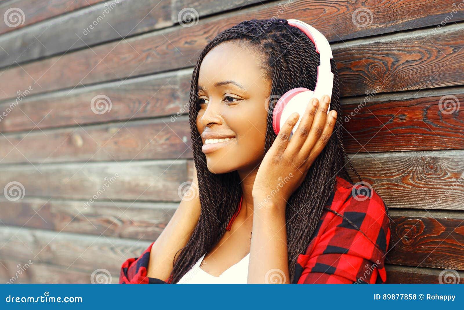 O retrato que da forma a mulher africana de sorriso feliz com fones de ouvido está apreciando escuta a música sobre o fundo