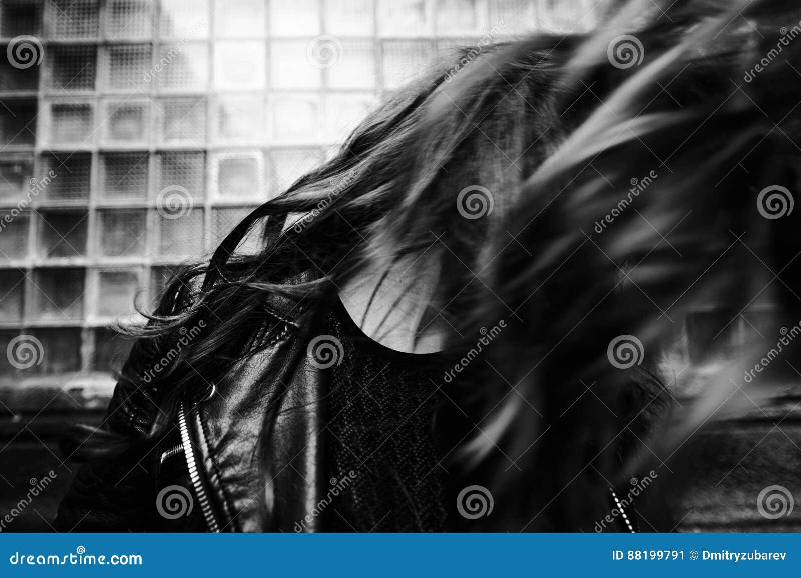 O revestimento vestindo do motociclista da mulher bonita oriental levanta no quintal da casa de apartamento do vintage