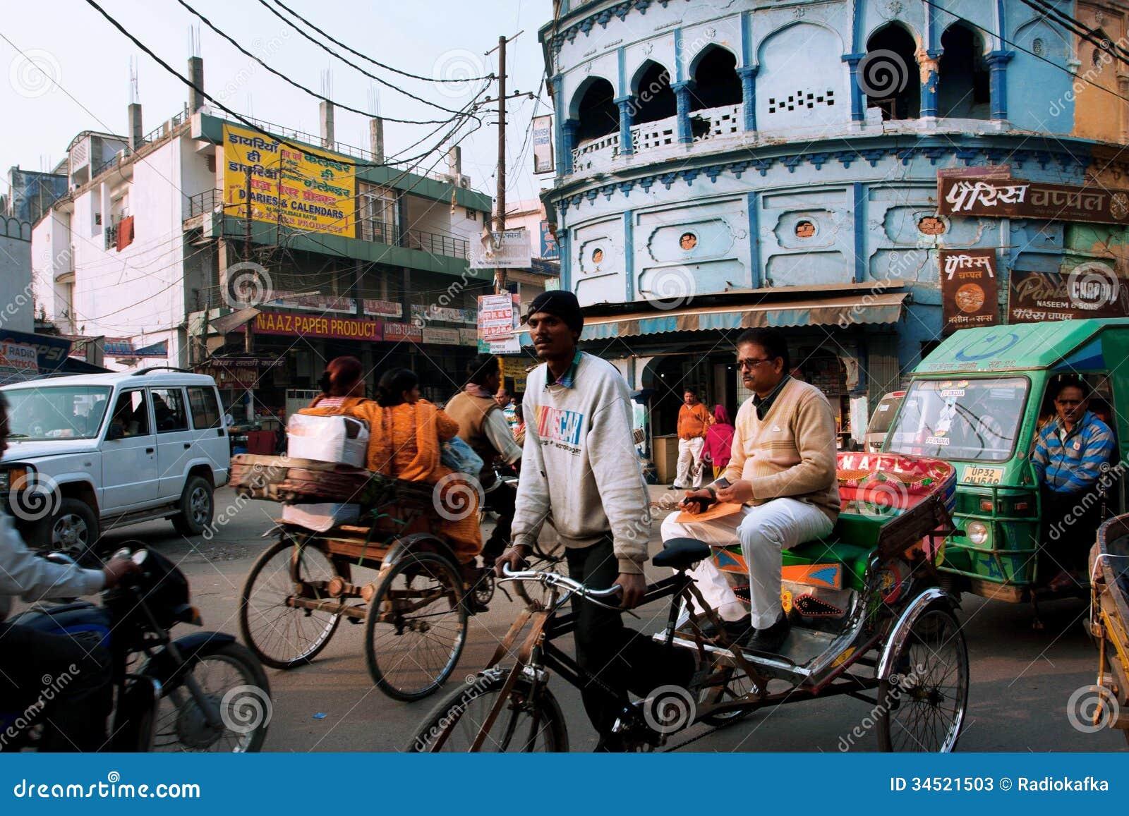 O riquexó conduz através da rua aglomerada com muitas bicicletas em Lucknow, Índia