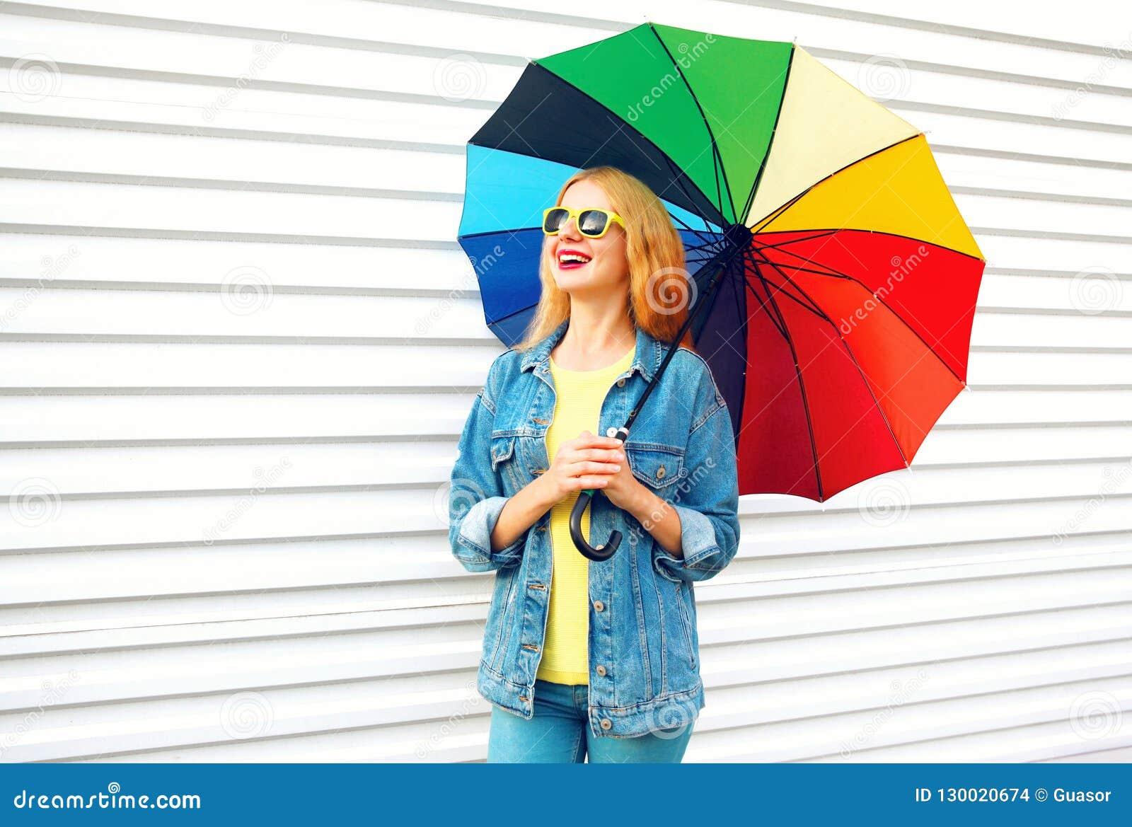O riso feliz da mulher guarda o guarda-chuva colorido, sonhos no branco