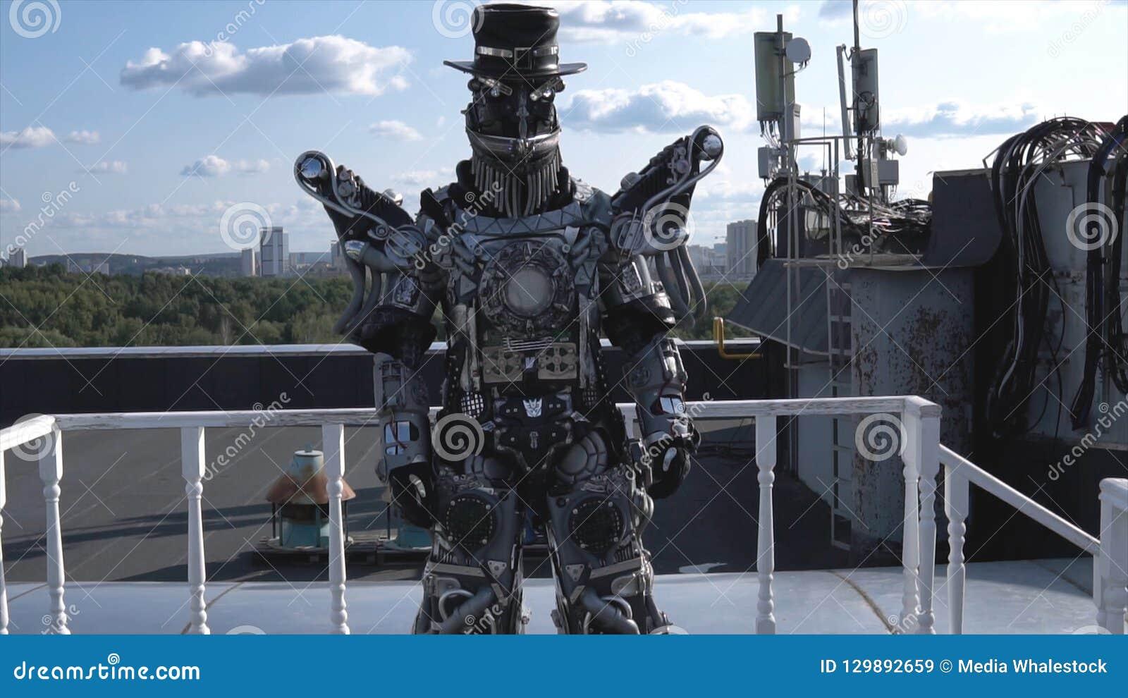 O robô humano em todo o crescimento é conduzido pelos membros no fundo do céu azul com nuvens footage Android com cara e chapéu