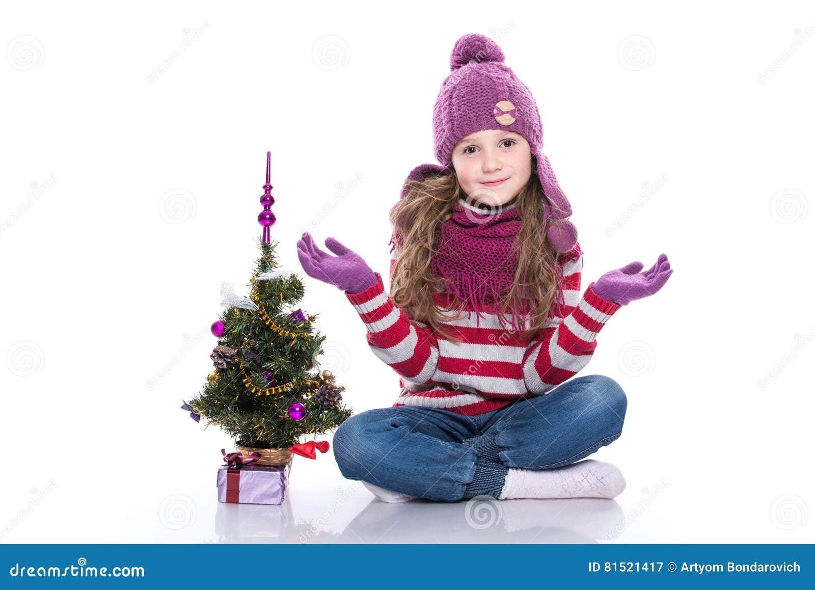 O roxo vestindo de sorriso bonito da menina fez malha o lenço e o chapéu, sentando-se perto da árvore de Natal e do presente isol