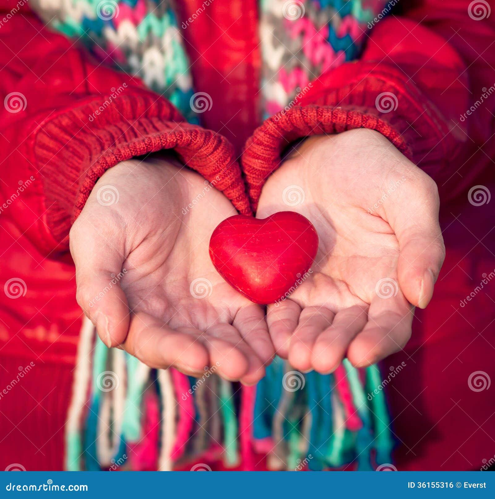 O símbolo do amor da forma do coração na mulher entrega o dia de Valentim