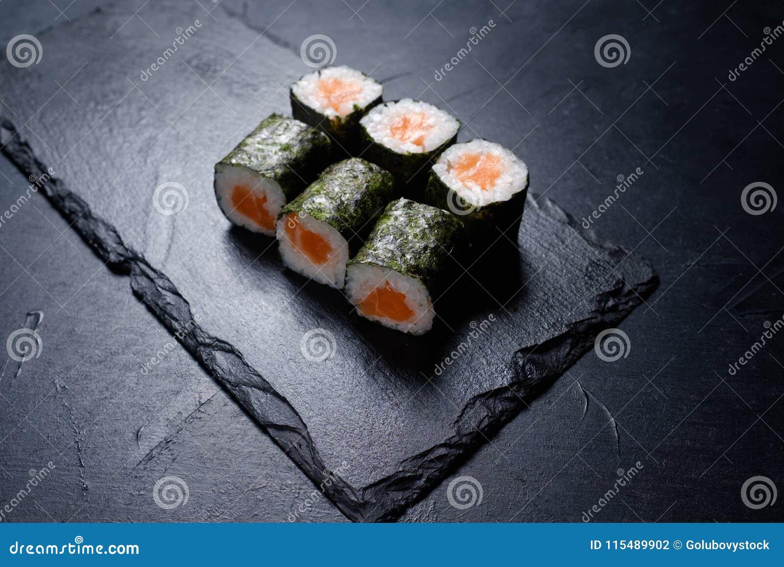 O salmão do sushi rola a culinária escura do asiático do fundo