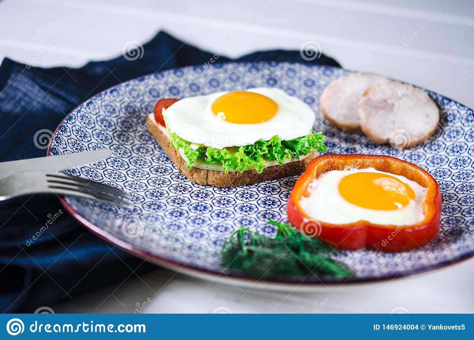 O sandu?che com ovo, presunto, queijo, brinde e salada deixa mentiras em uma placa com o tomate e o aneto