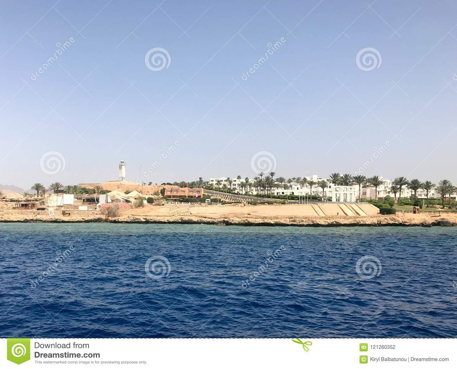 O seascape das montanhas de pedra marrons bonitas distantes e das várias construções na costa e no mar azul dos azuis celestes de