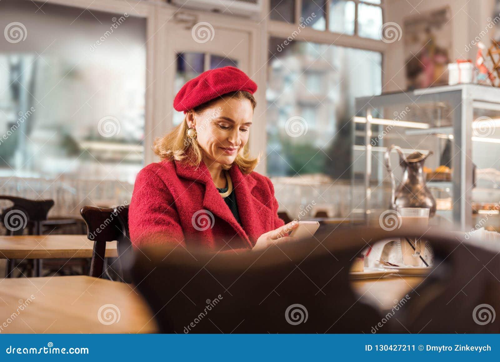 O sentimento à moda atraente maduro da mulher relaxou o assento na padaria no fim de semana