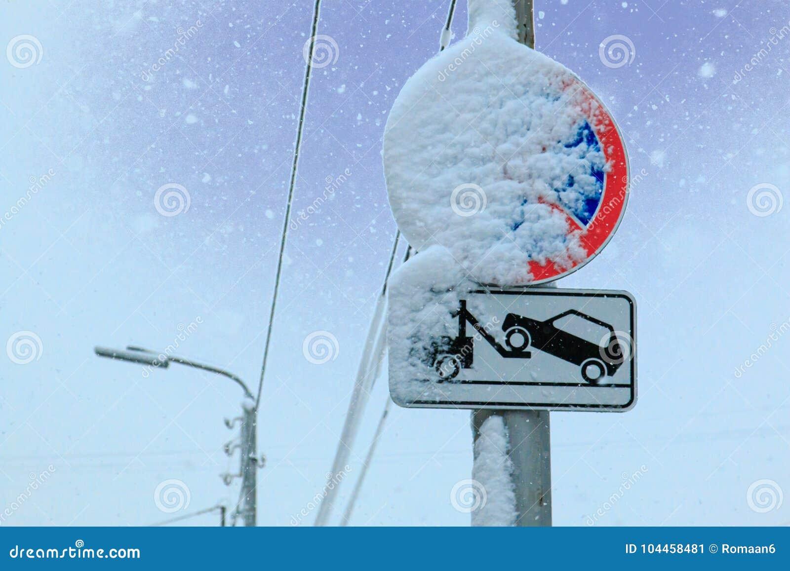 O sinal de estrada uma parada é proibido e o caminhão de reboque é levado pela neve em um fundo do céu