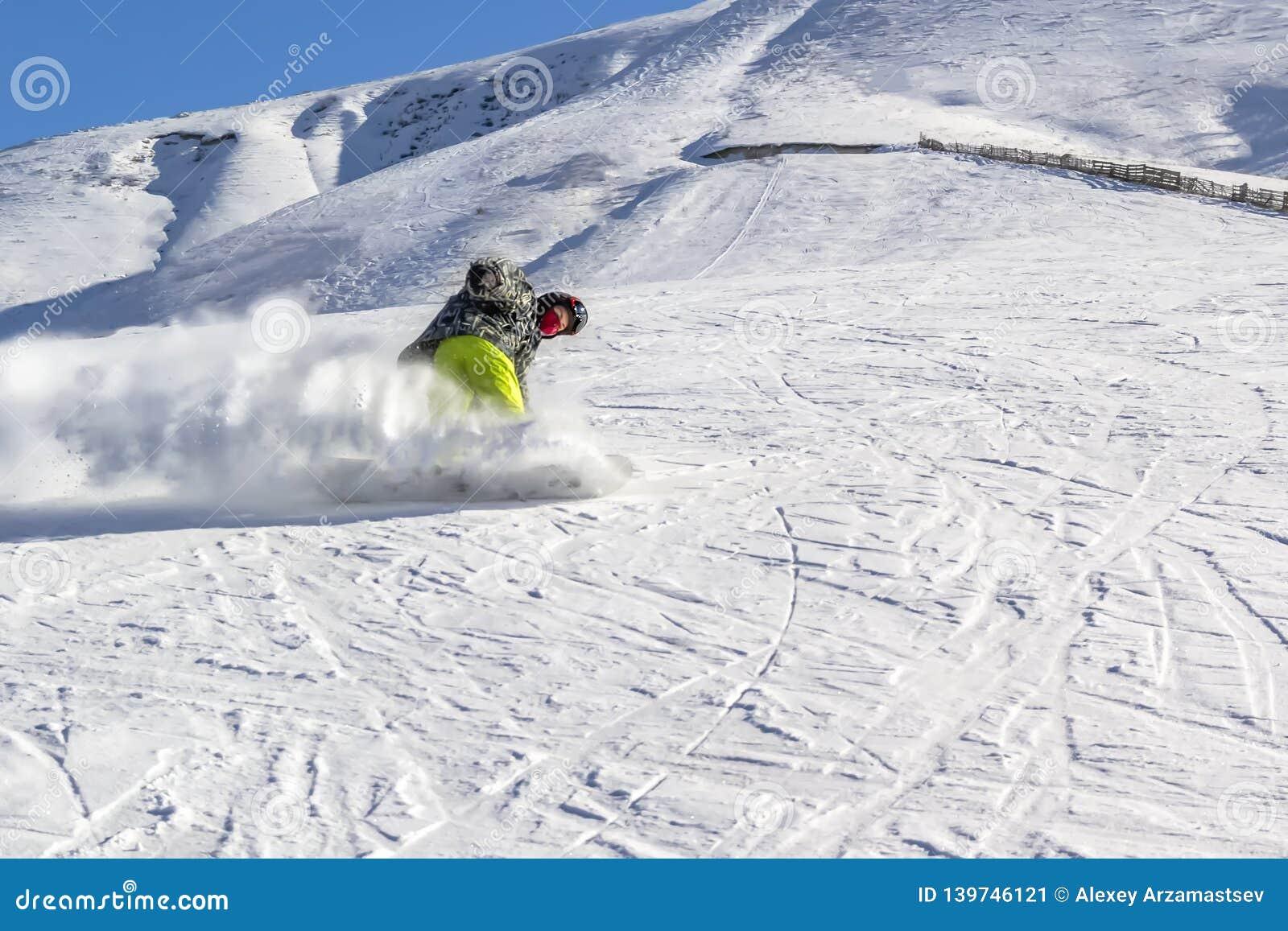 O Snowboarder rola rapidamente para baixo em uma nuvem da poeira da neve contra um céu azul em um dia ensolarado