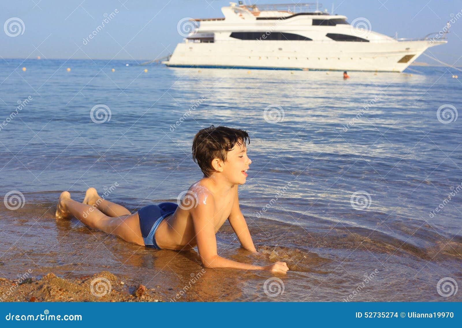 O sol considerável do preteen bronzeou-se a natação do menino na praia do mar do Res