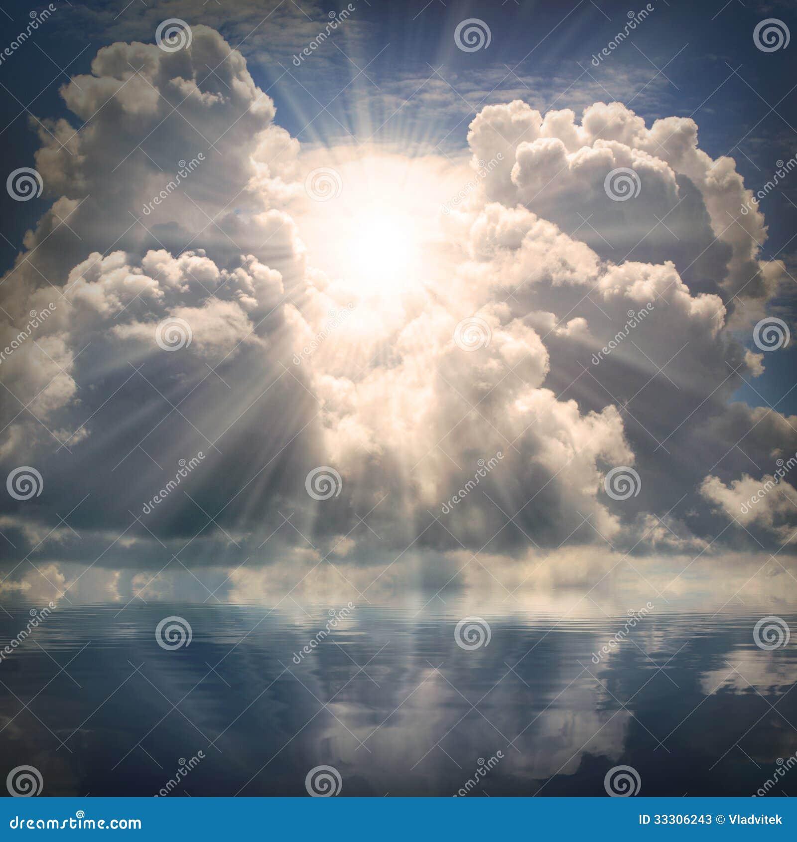 O sol no céu dramático sobre o mar.