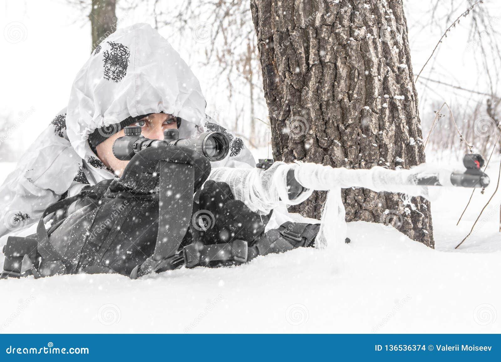 O soldado do homem do close up no inverno em uma caça com um rifle de atirador furtivo na camuflagem branca do inverno encontra-s