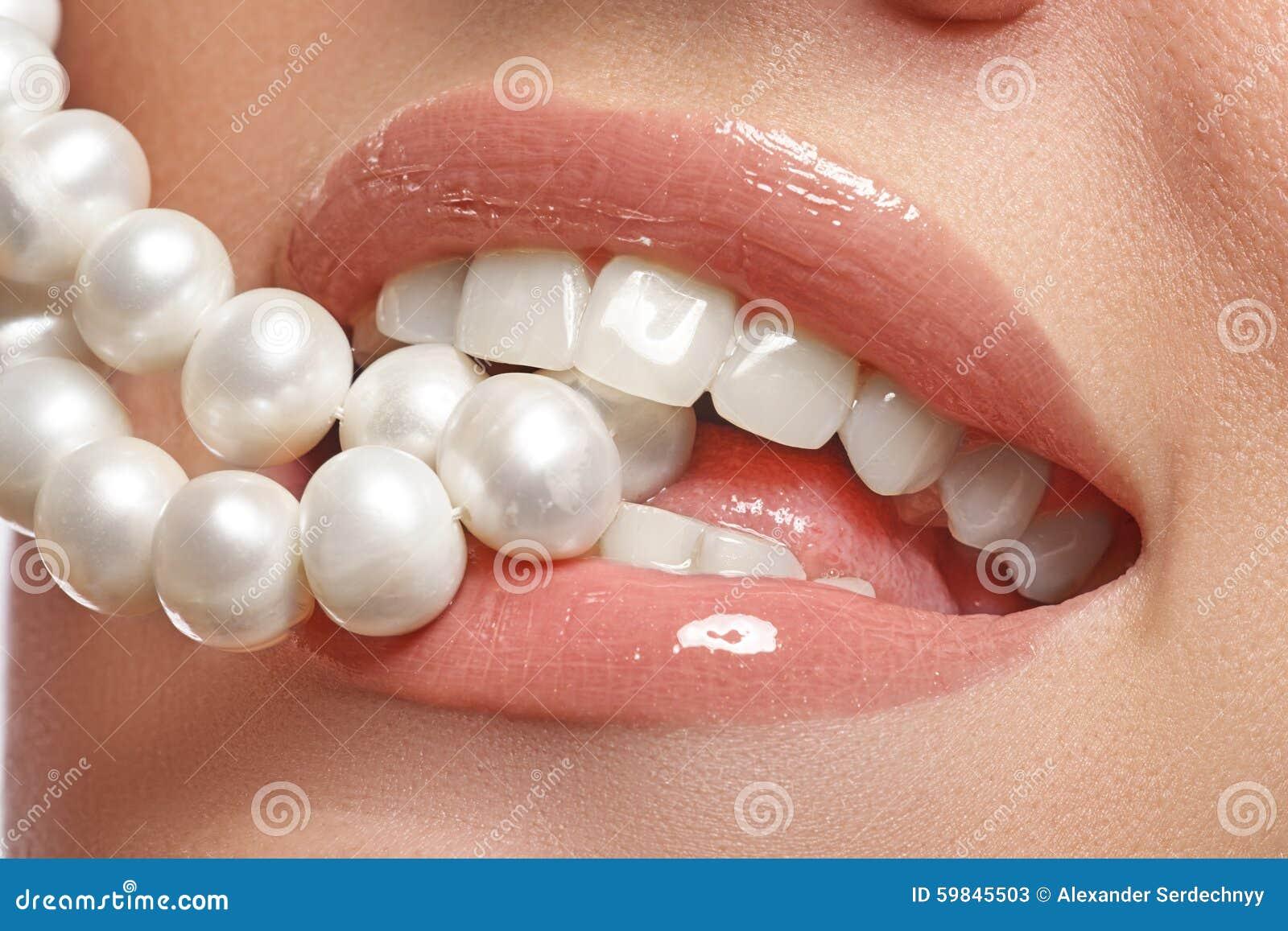 O sorriso fêmea feliz do close-up com os dentes brancos saudáveis, os bordos vermelhos brilhantes prepara Cuidado da cosmetologia