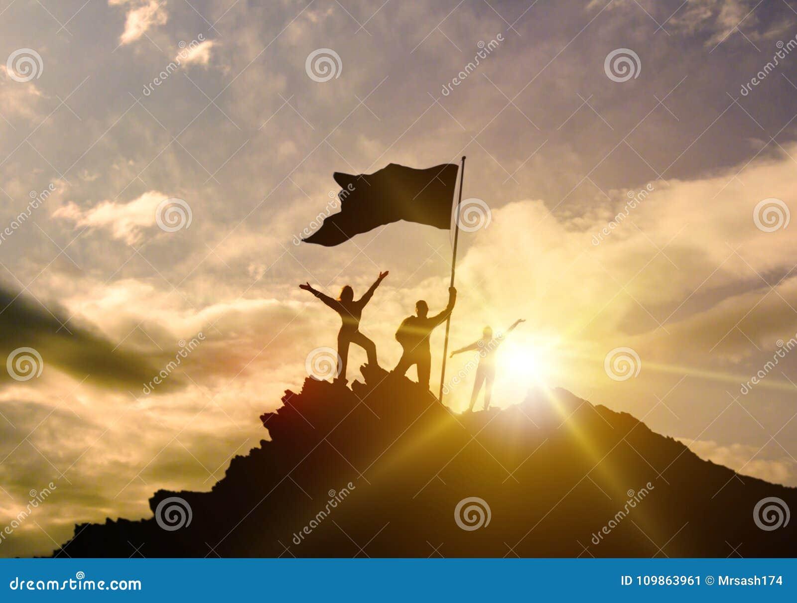 O sucesso alto, família três mostra em silhueta, pai da mãe e criança que mantém a bandeira da vitória sobre a montanha, mãos