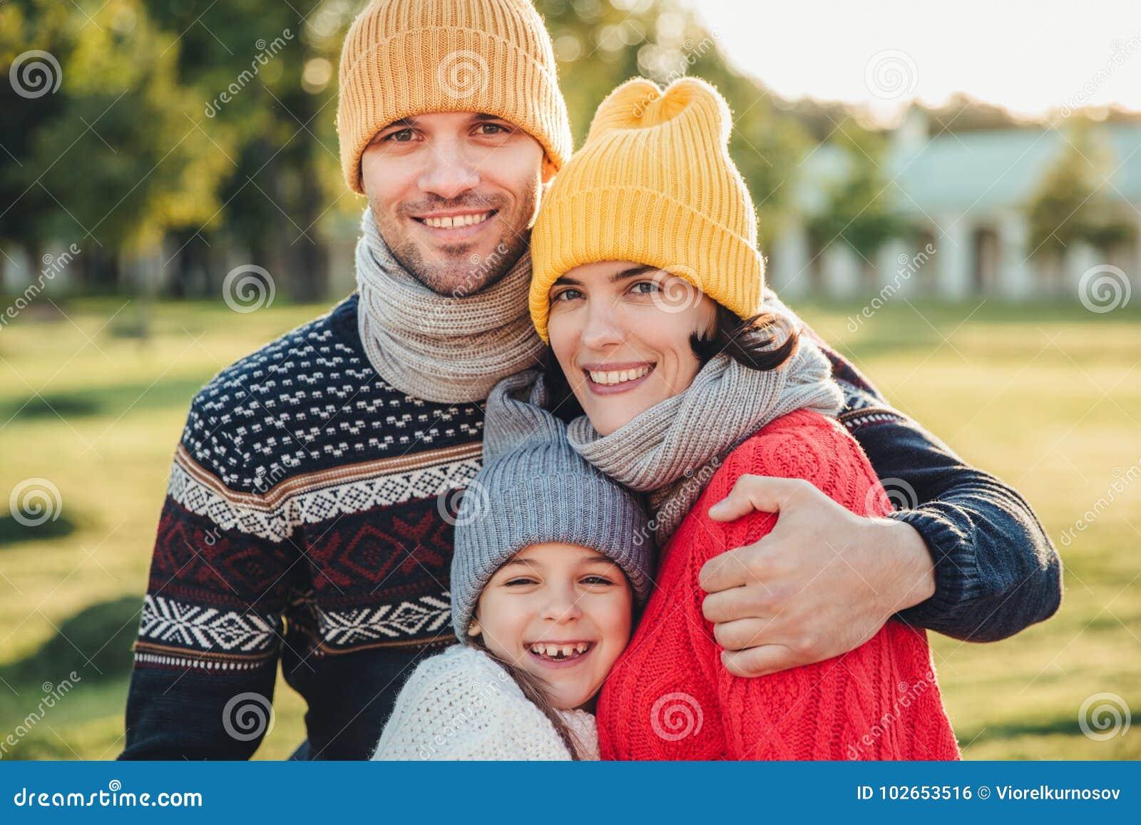 O suporte adorável da criança pequena perto de seus pais afetuosos, aprecia passar o tempo junto, abraça-se, sorriso felizmente,