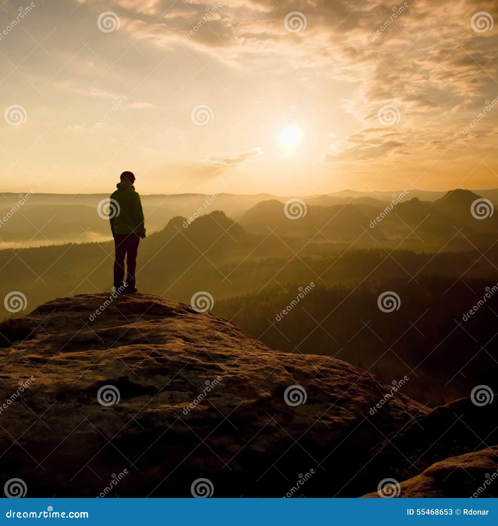 O suporte do caminhante no canto afiado da rocha do arenito em impérios da rocha estaciona e olhando sobre o vale enevoado e nevo