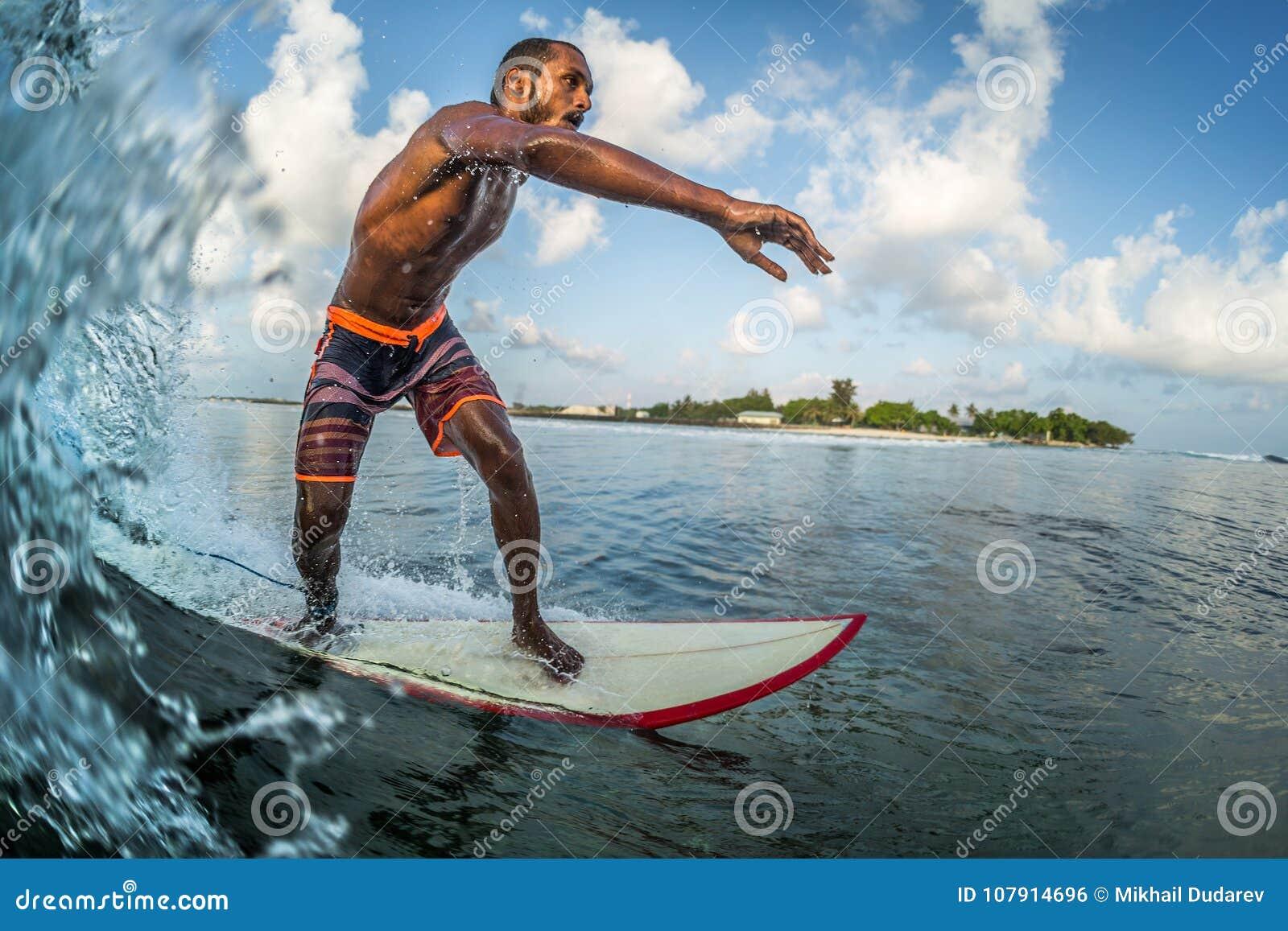O surfista profissional asiático monta a onda de oceano