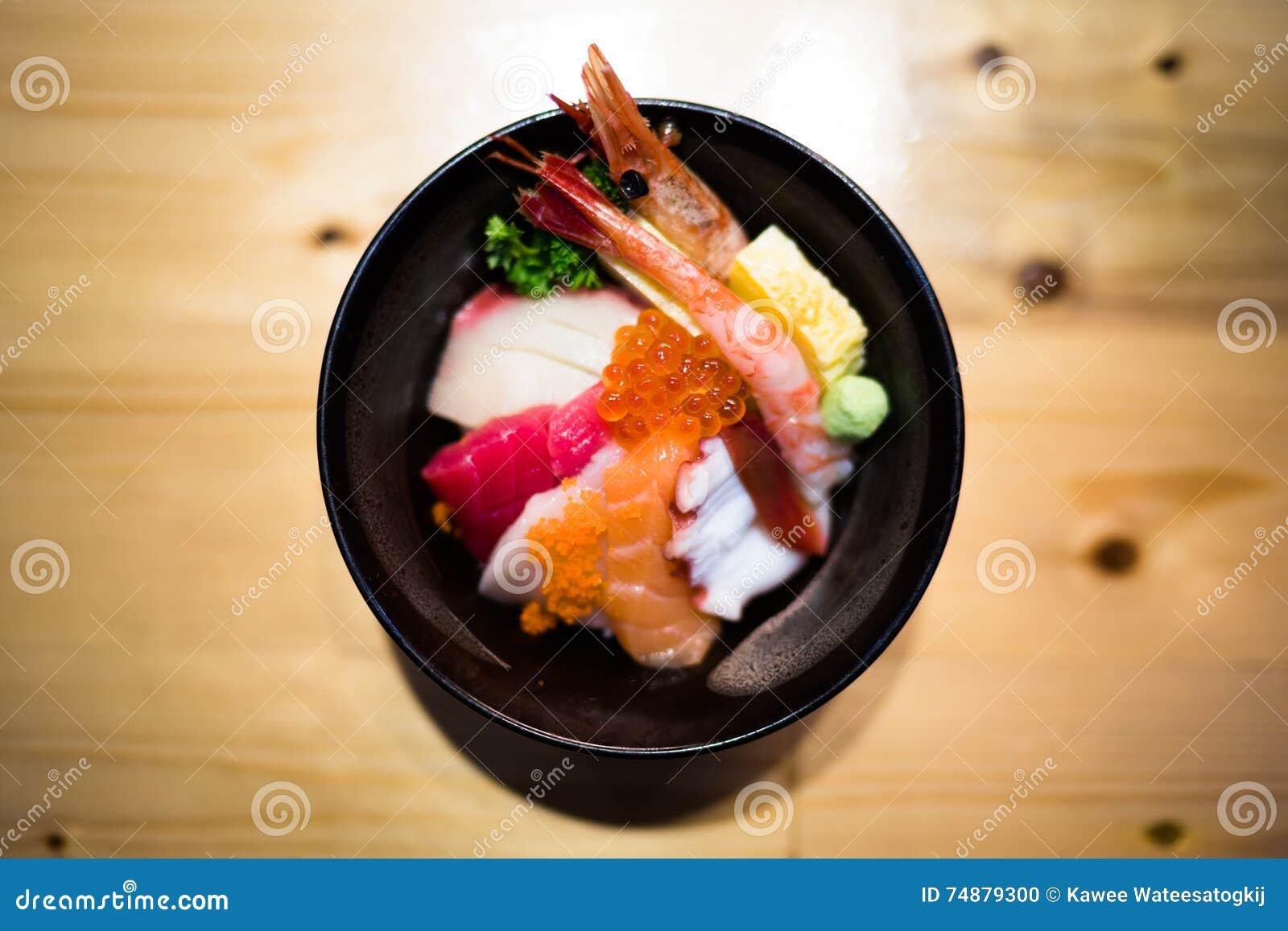 O sushi de Chirashi, bacia de arroz japonesa do alimento com o sashimi salmon cru, marisco misturado, vista superior, escurece a