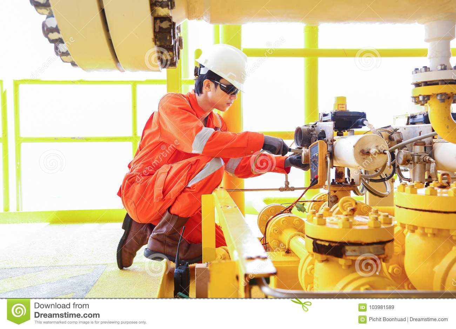 O técnico bonde e do instrumento está substituindo a válvula de solenoide da válvula interrompida na plataforma do telecontrole d