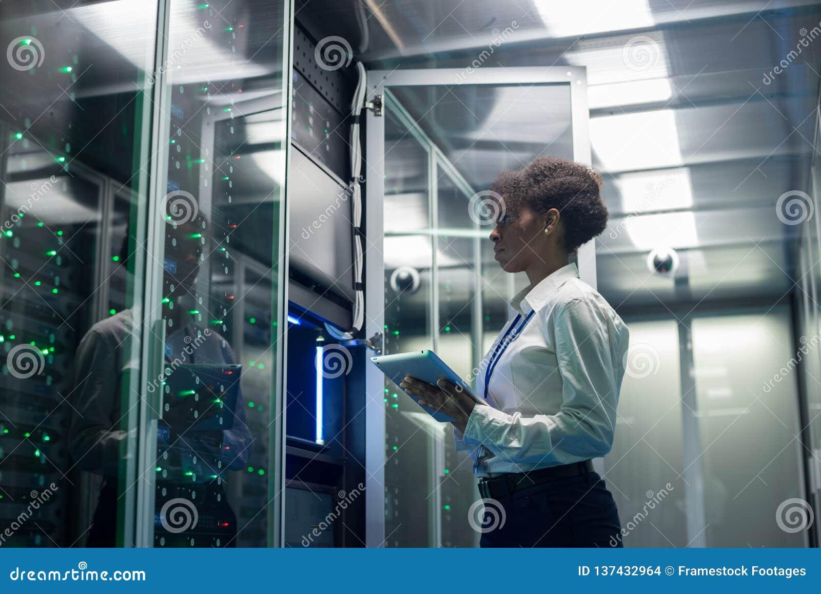 O técnico fêmea trabalha em uma tabuleta em um centro de dados