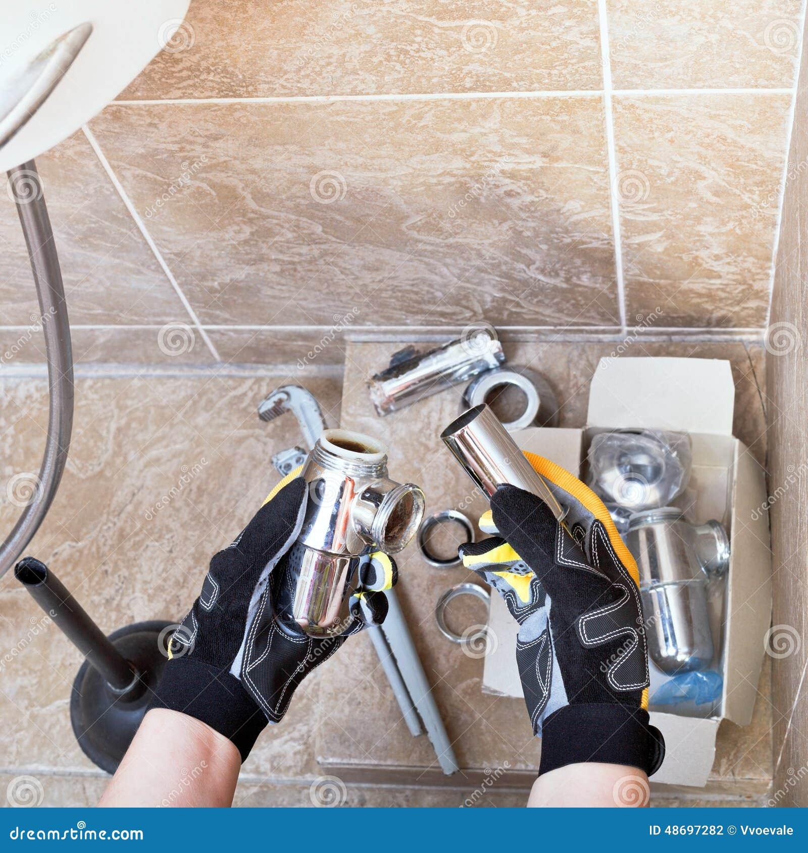 O técnico sanitário repara a armadilha do encanamento