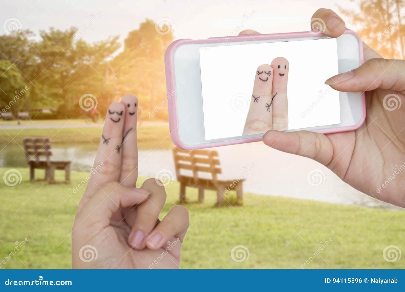 O telefone esperto do uso da mão toma a foto amantes engraçados do dedo