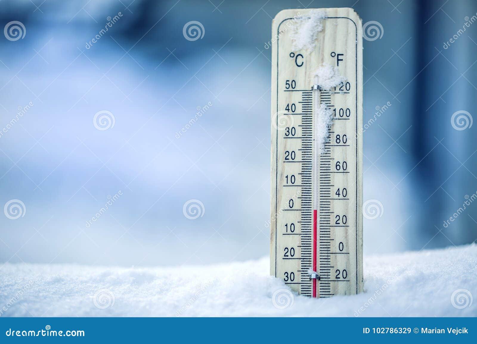 O termômetro na neve mostra as baixas temperaturas - zero Baixas temperaturas nos graus Celsius e Fahrenheit Tempo frio do invern