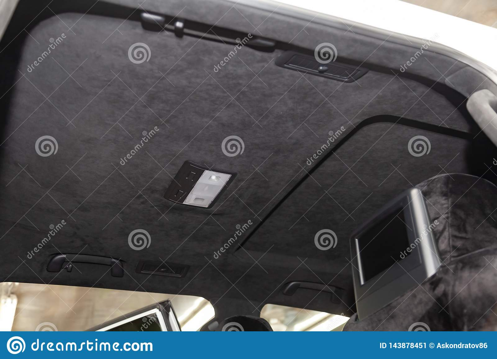 O teto do carro de SUV puxado pelo alkantara material macio preto na oficina para ajustar e denominar o interiorof