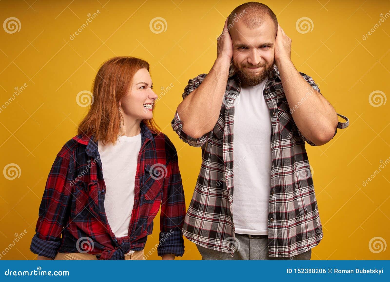 O tiro da mulher vermelha irritada irritada do cabelo censura o marido, acusa em algo gritos com aborrecimento, homem não barbead