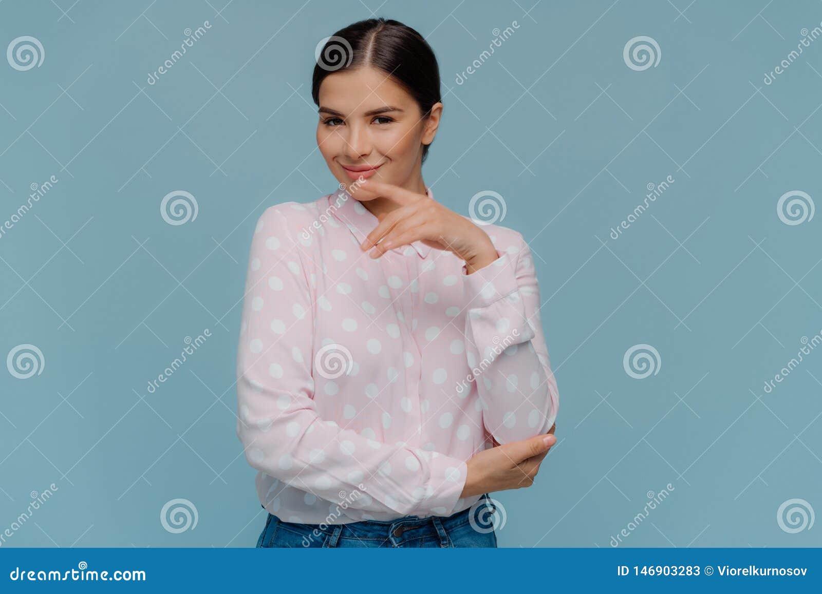 O tiro do estúdio do queixo fêmea seguro de vista agradável dos toques delicadamente com dedo dianteiro, vestido na camisa do às