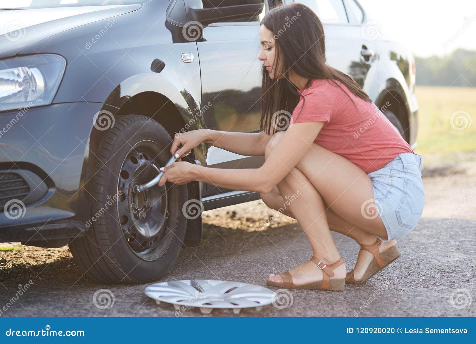 O tiro do motorista fêmea experiente novo bonito tenta mudar a roda de carro, usa ferramentas necessárias ou o equipamento, para