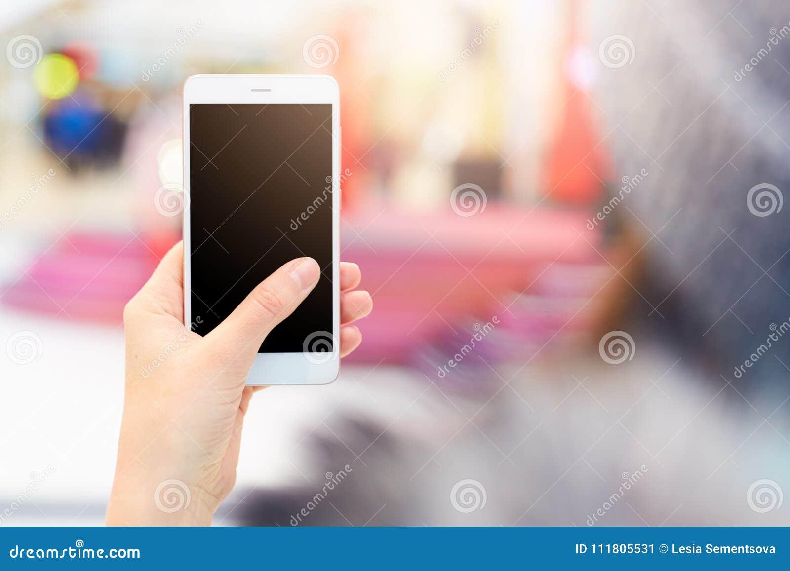 O tiro do telefone celular moderno das posses irreconhecíveis da mulher com a tela preta vazia olha o vídeo ou vê fotos, meios so