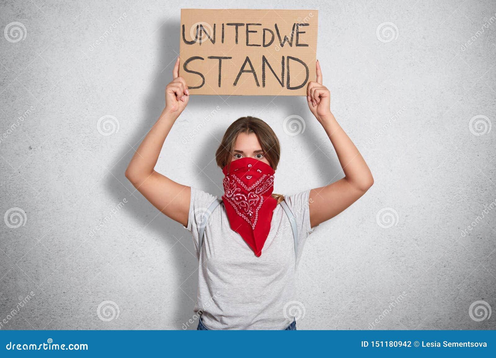 O tiro interno da mulher feminista corajoso que levanta o sinal com inscrição uniu-nos está, chamando para a unidade, vestindo a