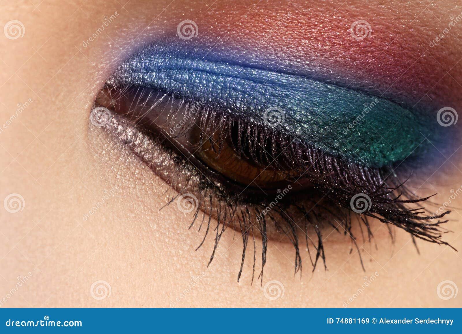 O tiro macro de cores bonitas do olho do ` s da mulher, as brilhantes e as profundas faz