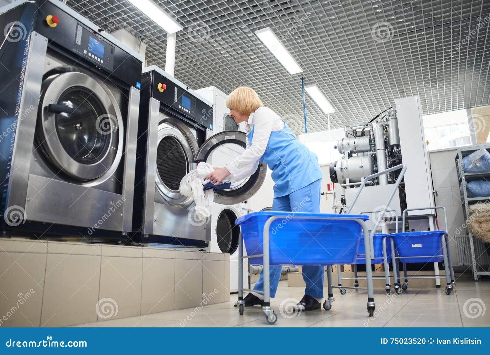 O trabalhador carrega a roupa da lavanderia na máquina de lavar