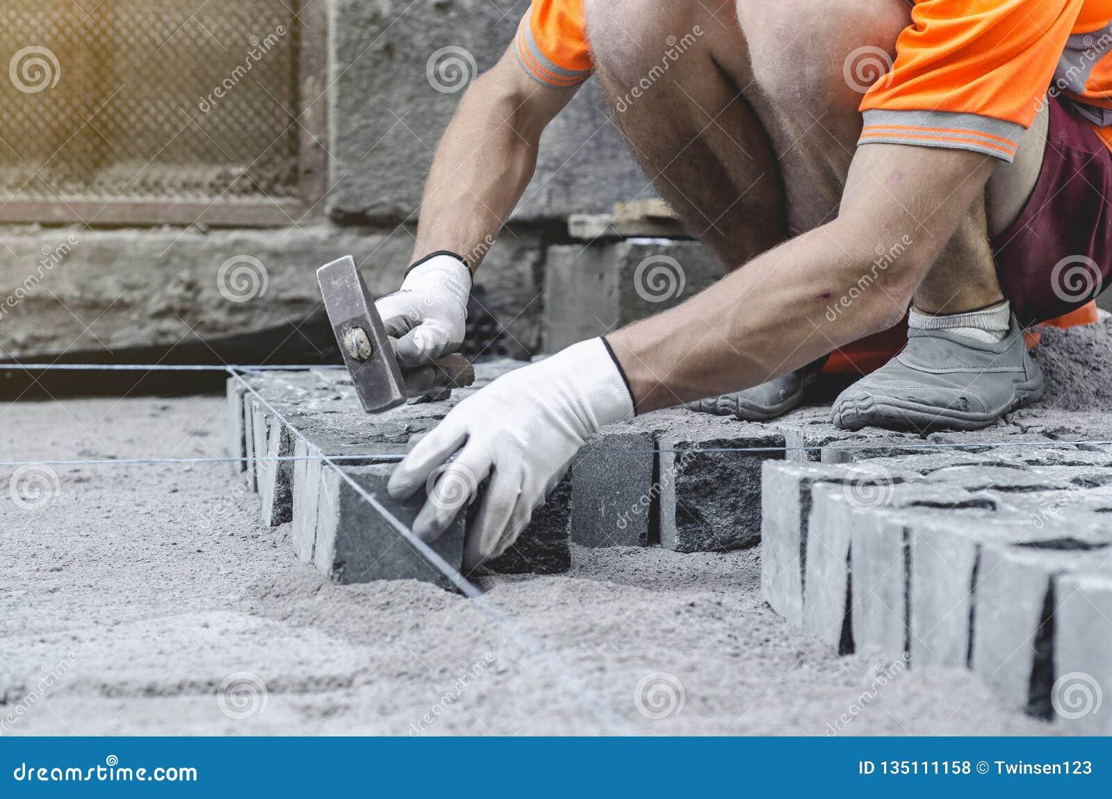 O trabalhador coloca telhas cinzentas do pavimento do granito no local marcado Arranjo do ambiente urbano Reparo de estradas de c
