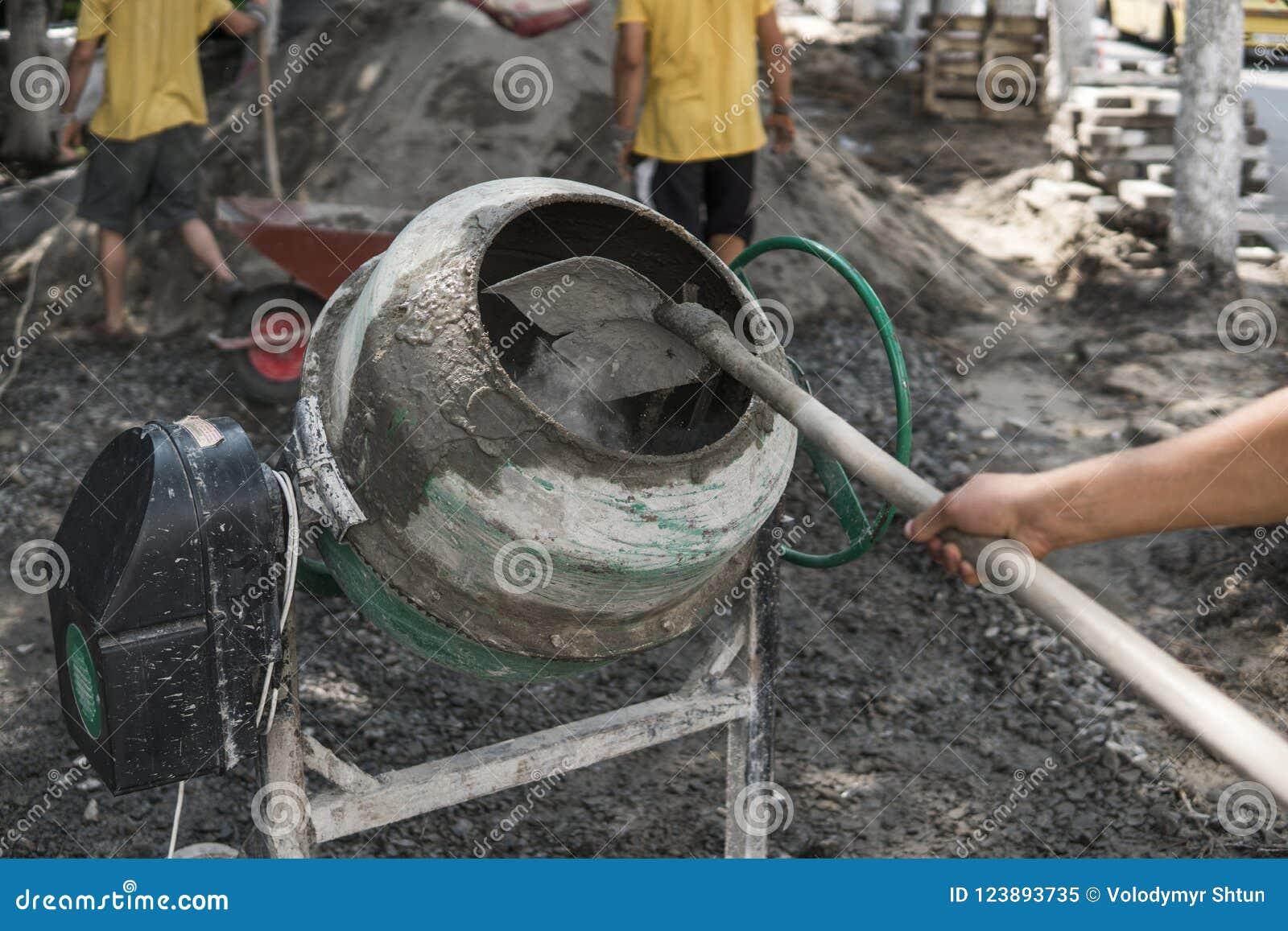 O trabalhador da construção adiciona ingredientes para misturar no misturador concreto no terreno de construção usando a pá duran