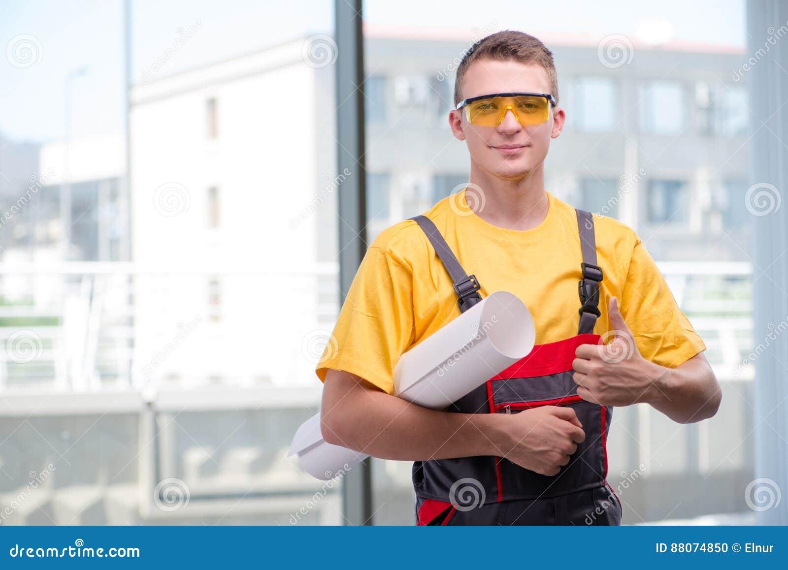 O trabalhador da construção novo em combinações amarelas