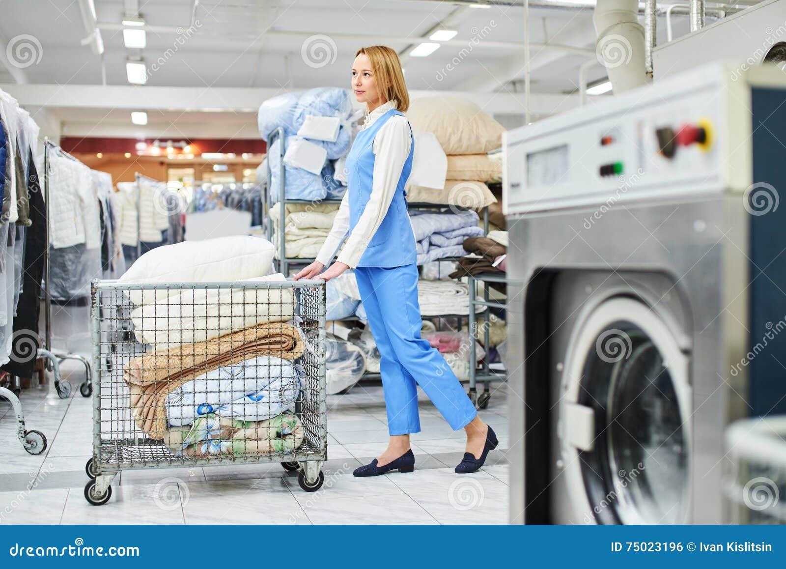 O trabalhador da lavanderia da menina rola um carro com material limpo
