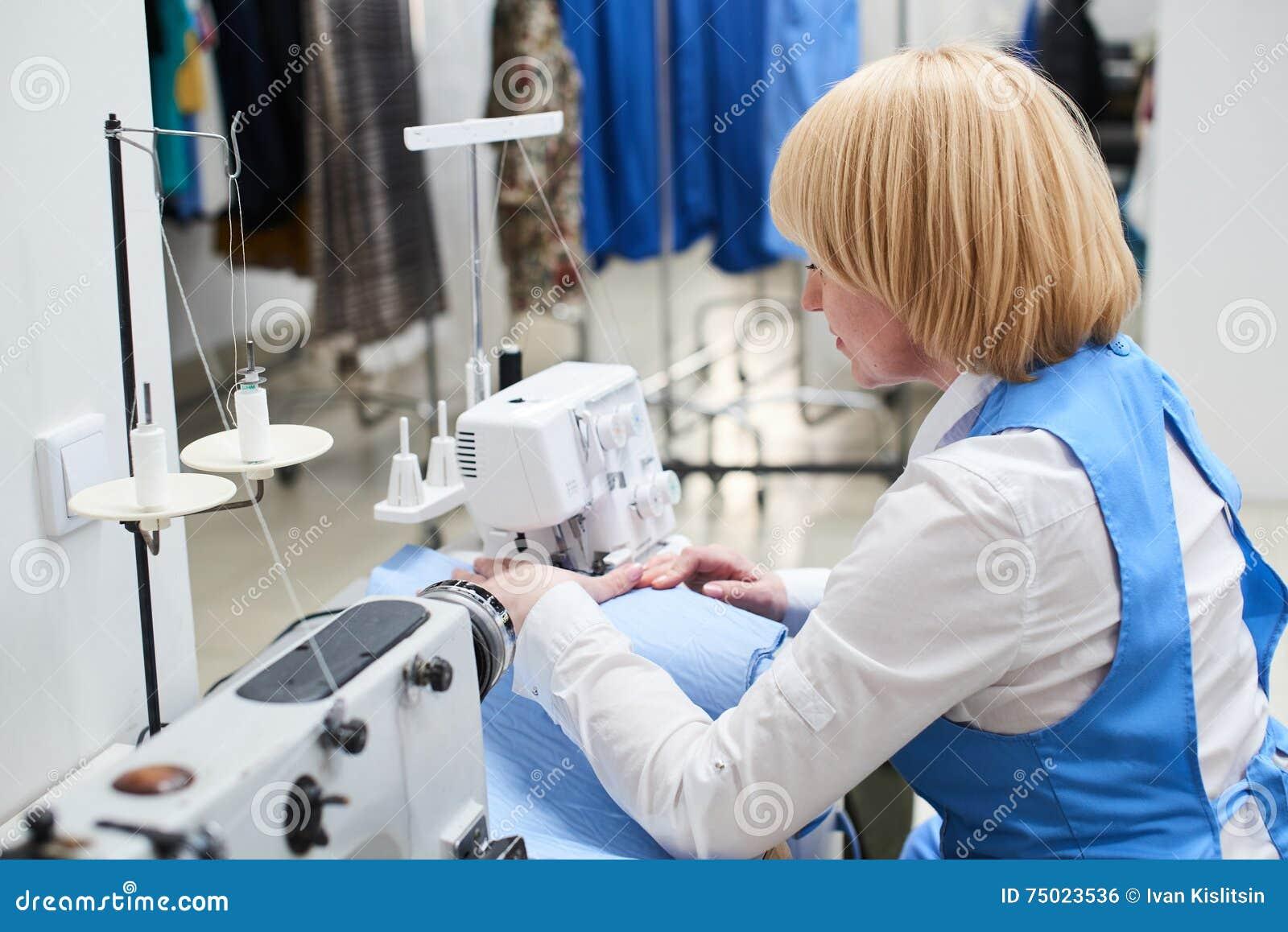 O trabalhador da lavanderia executa o reparo da roupa na máquina de costura