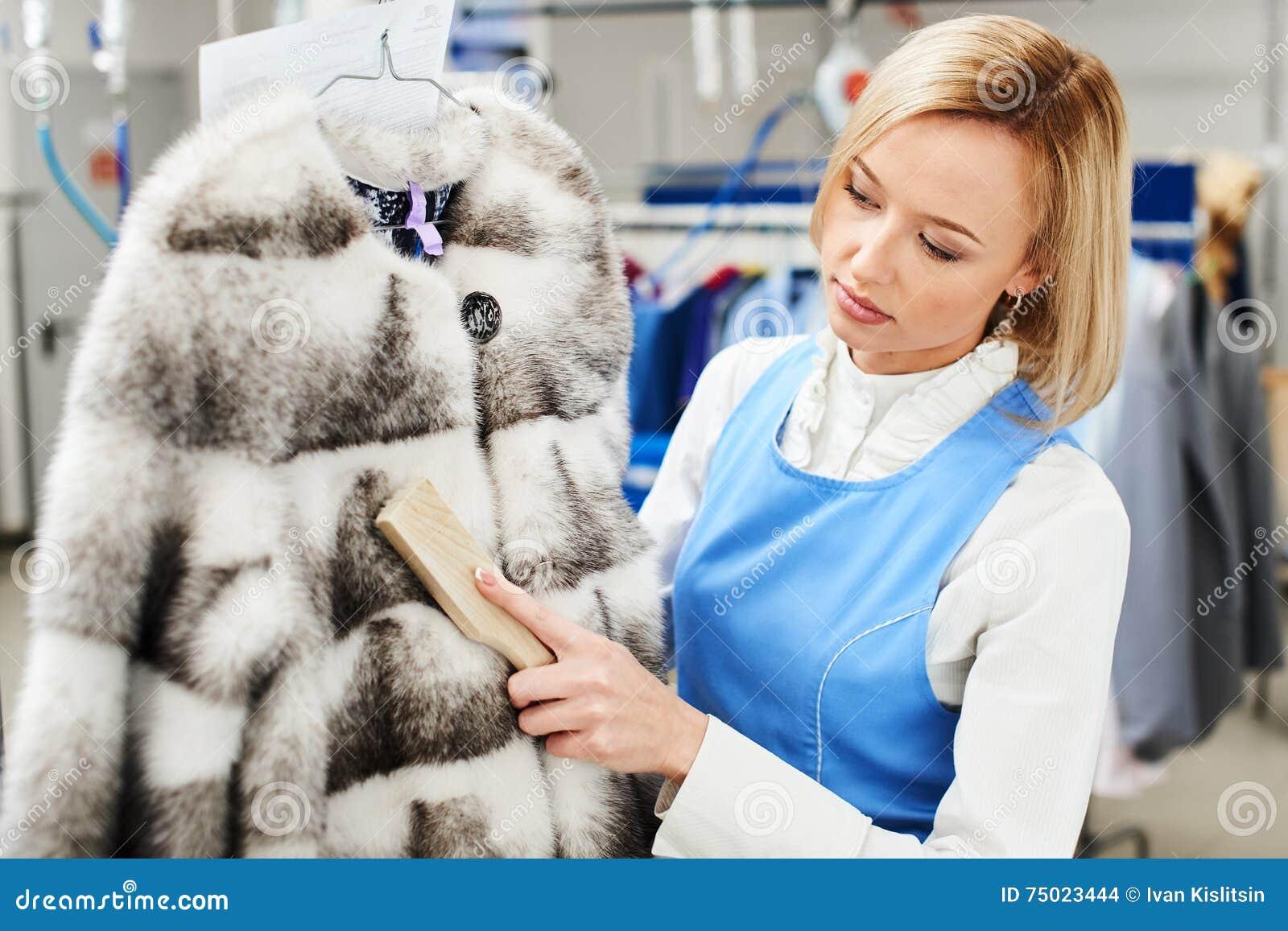 O trabalhador da menina executa a lavanderia seca, vestuários da pele da limpeza da mão