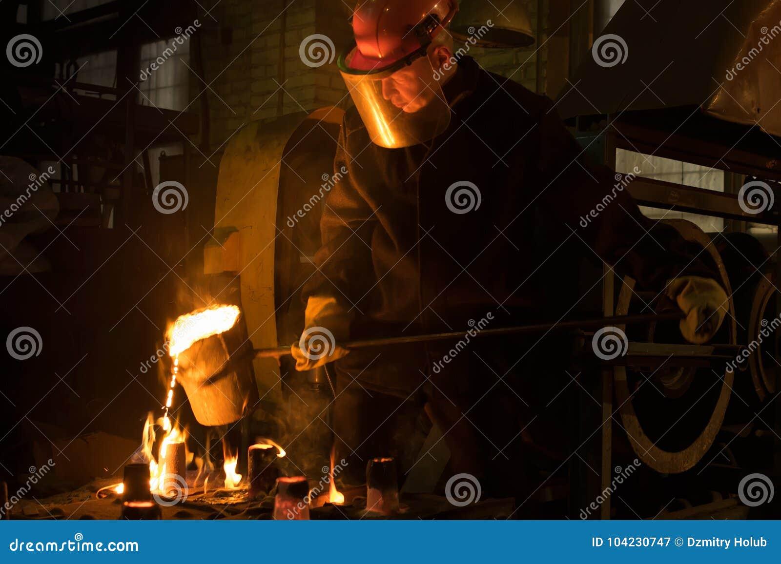 O trabalhador derrama o metal derretido da concha no molde