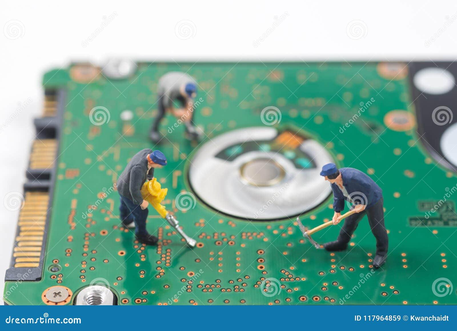 O trabalhador diminuto está escavando um furo no varrão eletrônico do disco rígido