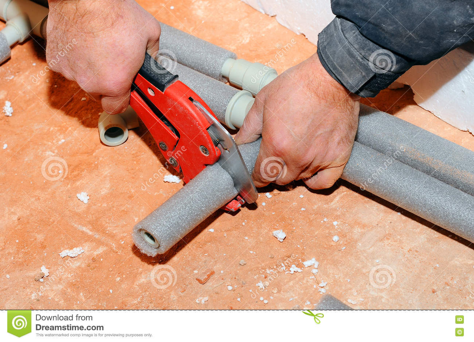 O trabalhador do encanador com tesouras corta o tubo tubulação do metal-plástico do corte por tesouras vermelhas especiais Trabal