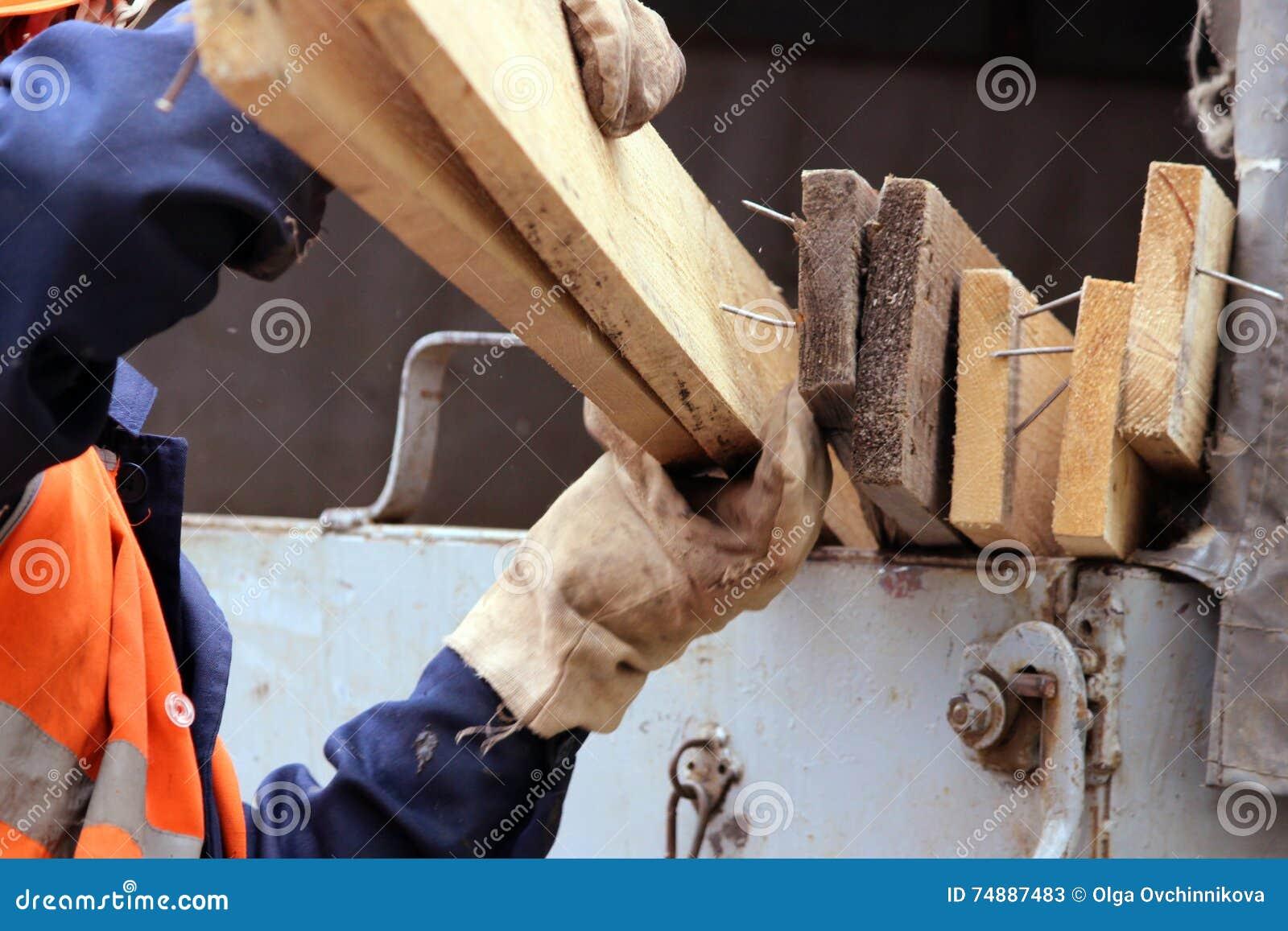 O trabalhador nas luvas está carregando pranchas no caminhão